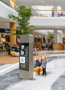 Mother and child using selfie application in shopping center