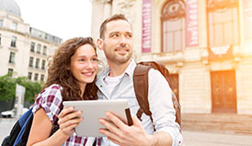 Tourist couple using a tablet with virtual tour application