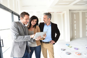 Sales person showing real estate app on tablet to couple on site